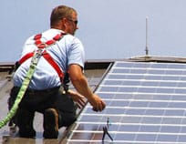 A PV panel fitter on the roof